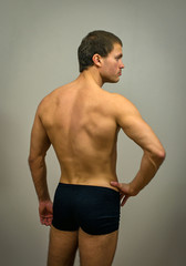 Muscular male model posing. Back view.