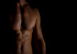 Unrecognizable muscular male body on black background.