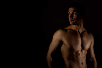 Muscular male model on black background. Place for your text.