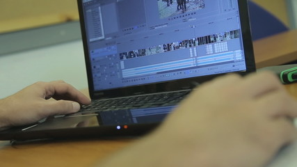 Man working on laptop with video editing software
