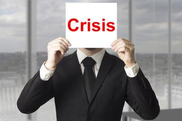businessman hiding face behind sign crisis