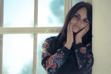 Mujer bella pensativa en la ventana