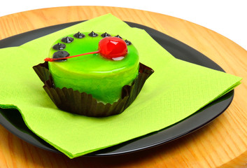 Delicious green cake with cherry on black plate on cutting backg