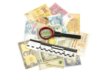 bills and magnifier with ruler of forensic