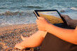 young girl and her tablet with love picture on beach