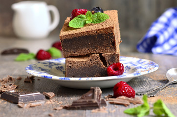 Brownies decorated with raspberry and mint leaf.