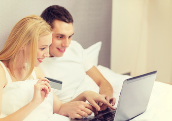 couple in bed with laptop computer and credit card