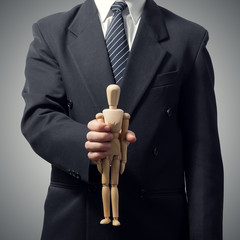 businessman holding little wooden mannequin