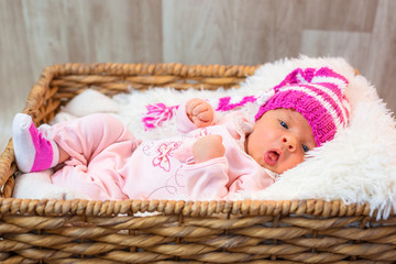 Newborn baby girl in a square wicker basket