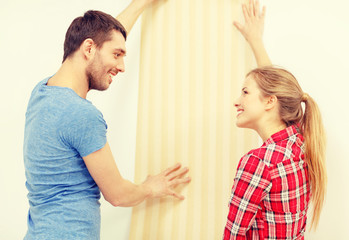 smiling couple choosing wallpaper for new home