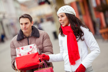 Excited young woman shopping with young man
