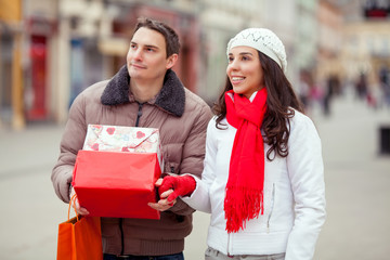 Young couple at the street holding gift boxes