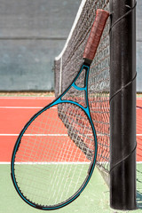Blue and black tennis racket leaning on metal pole by the net