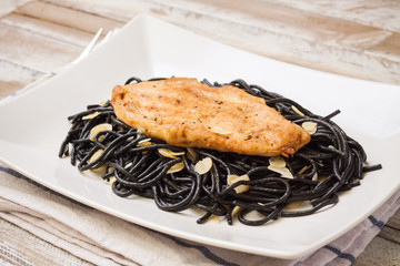 Grilled chicken with black spaghetti, maple syrup and almonds