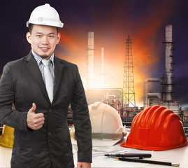 young petrochemical engineer standing in front of working tale o