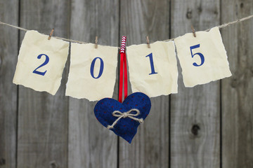 Year 2015 on antique paper and heart hanging from clothesline