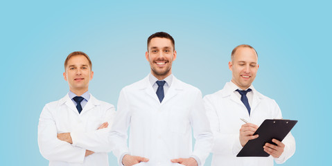 group of smiling male doctors in white coats