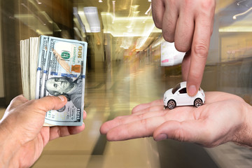 One man holding dollar banknotes, another man holding small car