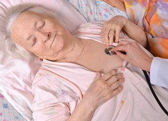 Nurse taking the heartbeat of old woman