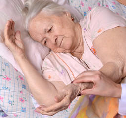 Female caretaker checking pulse of old woman at nursing home