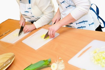 Two woman cutting onions on cutting board, isolated
