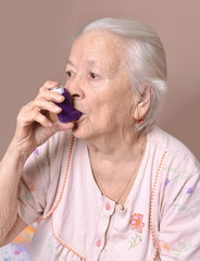 Old woman with asthma inhaler