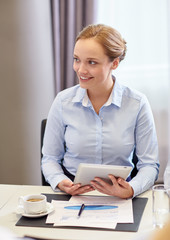 smiling woman holding tablet pc computer in office