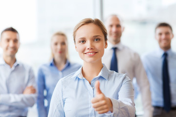 smiling businesswoman showing thumbs up in office