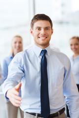 smiling businessman making handshake in office
