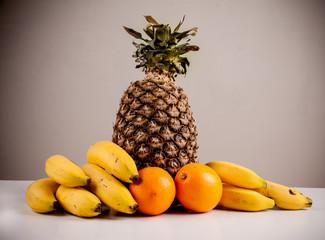 fruit , oranges, bananas , pineapple on gray background