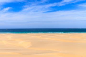 Sand dunes near to the ocean with cloudy blue sky, Boavista, Cap