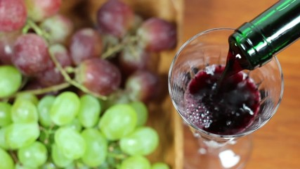 Red Wine Pouring Into A Glass. Grapes in background 2
