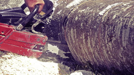 Man sawing wood chainsaw