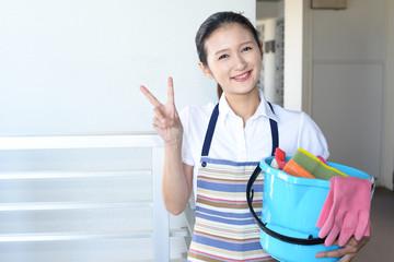 掃除用品を持つ笑顔の主婦