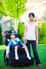 Disabled little boy in wheelchair with sister on grassy lawn out