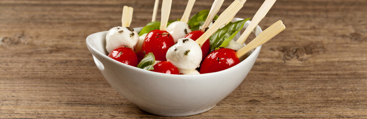 Caprese salad on a sticks with mozzarella, tomatoes and basil