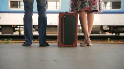 Pair at the station with a suitcase