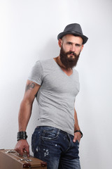 Portrait of handsome bearded man in hat standing with bad,