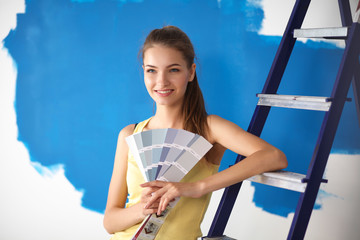 Young beautiful woman holding color palette , standing near wall