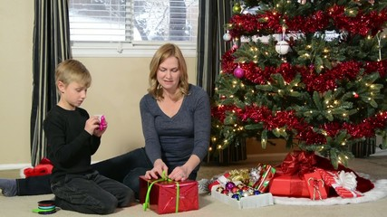 Mother teaching a child to tie a bow on a Christmas present