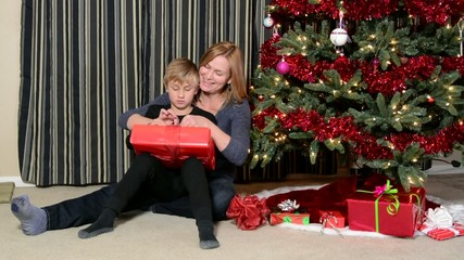 Mother and child open a gift by the Christmas tree