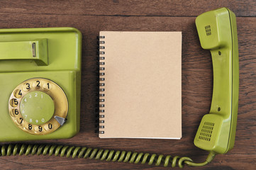 Vintage rotary telephone and notebook on wooden background.