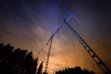 Power lines at night with starry sky