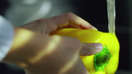 Female hands washing a yellow pepper