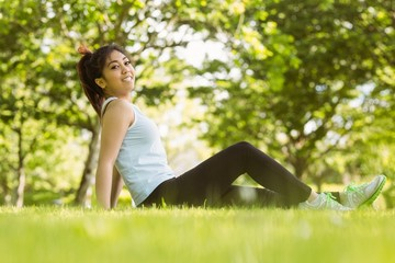 Healthy woman sitting on grass in park
