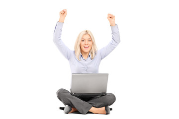 Woman working on laptop and gesturing joy