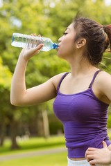 Healthy woman drinking water in park