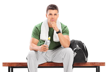 Young athlete holding water bottle seated on bench