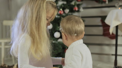Cute little girl playing with her baby sister near Christmas