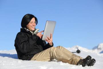 Happy hiker woman browsing a tablet on the snow